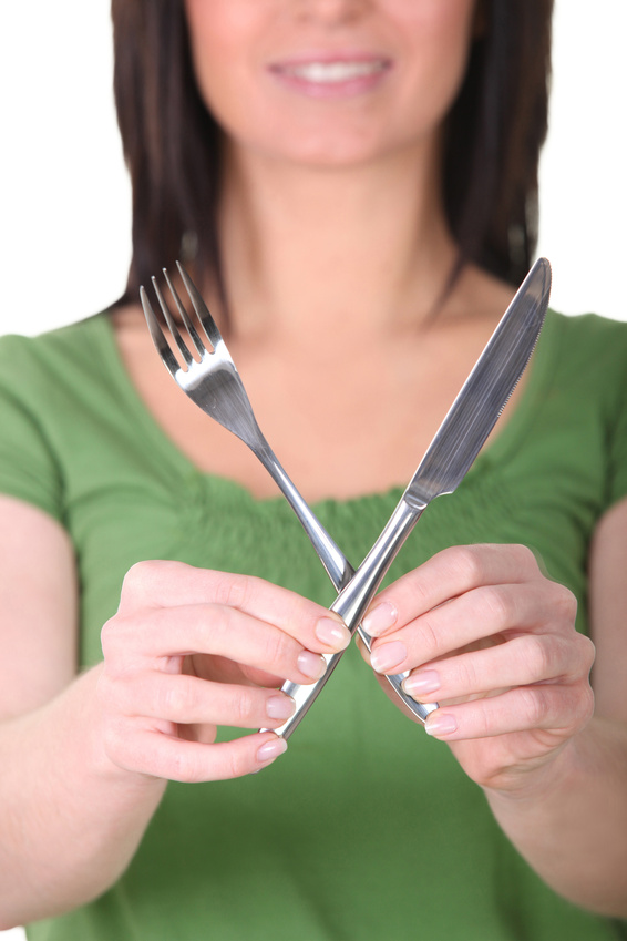 Woman holding up a knife and a fork