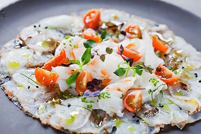 Làmines de bacallà confitat amb oli de raïm sobre carpaccio de bacallà amb vinagreta de llima perlada i germinat de ceba. Hotel Gallery