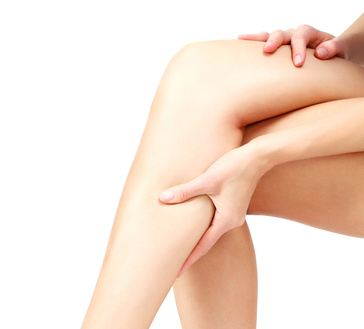 Pain in a leg, woman holding sore shin, white background
