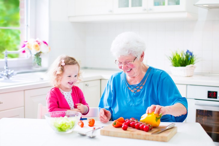 Adorable grandmother and little cute girl making salad