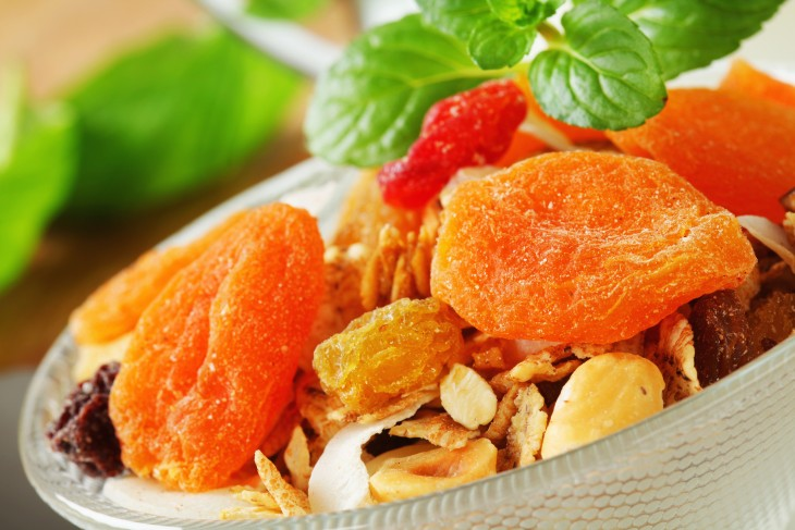 Bowl of rolled oats with various dried fruit pieces and nuts