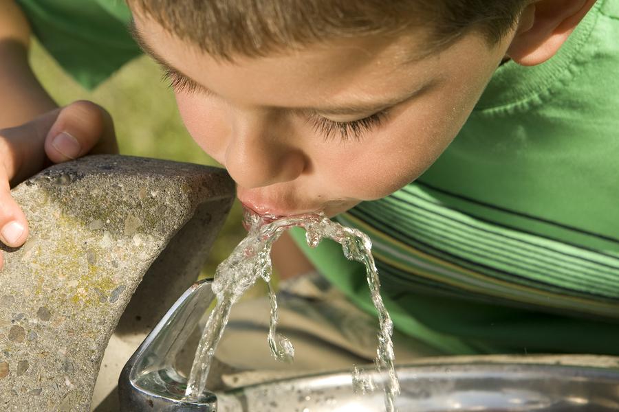 Nen bebent aigua d'una font pública