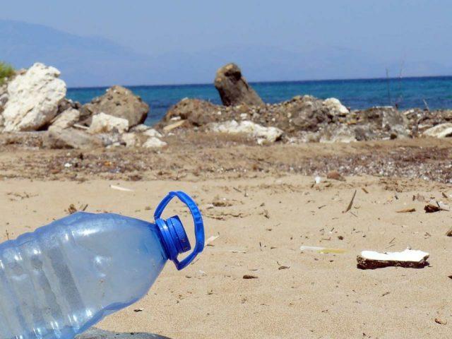 Ampolla de plàstic a la sorra de la platja. Necessitem una solució ja!