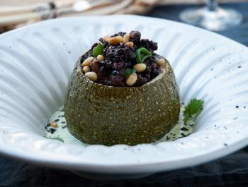 Carbassó rodó farcit d'arròs Nerone amb bolets xiitake, salsa al grill amb julivert i coriandre. Sal de sèsam negre.